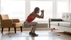 young woman doing squat work out inside her home